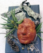 mask surrounded by bark,  pine cones, rocks, feathers, and foliage